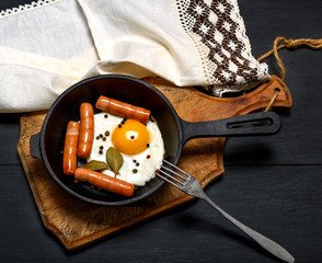 fried chicken egg with sausages in a round frying pan