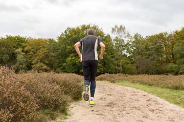 Elderly man running on a sandy path at the Blaricummerheide