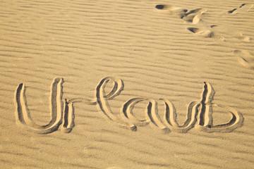 """""""Urlaub"""" in den Sand geschrieben"""