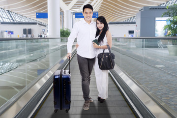 Happy couple wearing white standing on an airport travelator