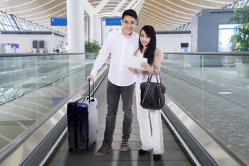 Happy couple wearing white going overseas standing on an airport travelator