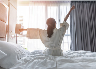 Easy lifestyle Asian woman waking up from good sleep in weekend morning taking some rest, relaxing in comfort bedroom at hotel window, having happy lazy day enjoying work-life quality balance concept