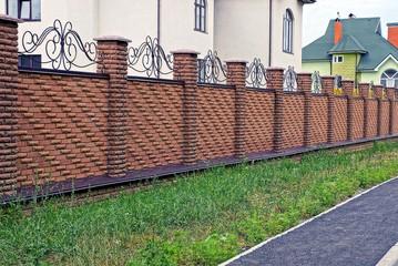 Brown rural brick fence near the house near the grass
