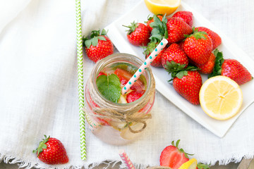 Mineral  water with fresh strawberries, lemon  and mint in jar on a white wooden background, copy space