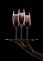 Hand holds tray with pink rosechampagne glasses