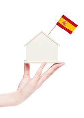 Female hand holding wooden house model with flag