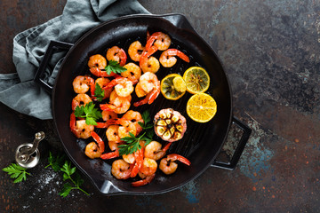 Prawns roasted on grill frying pan with lemon and garlic. Grilled shrimps, prawns. Seafood. Top view. Dark background