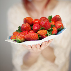 Beautiful woman hands holding a plate with strawberries in her hands, sensual studio shot can be used as background