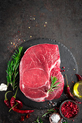 Aluminium Prints Meat Raw beef steak on black background with cooking ingredients. Fresh beef meat. Top view