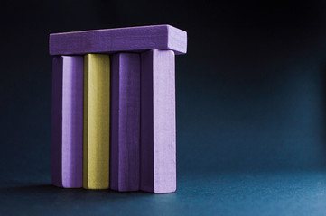 Side view of the yellow wood bar besieged with violet wood bars on the dark blue background. Concept of the racism, sexual discrimination, domination, social problems, emotional stress.