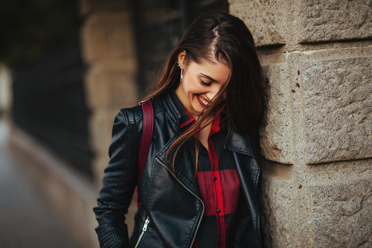 Portrait of a happy young woman in a leather jacket outdoor
