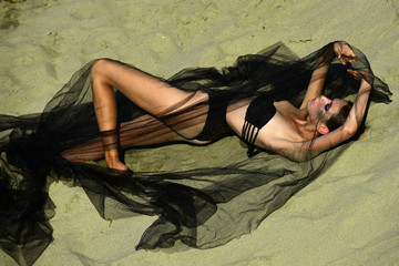 Fashion woman in swimsuit under black veil relax on sand