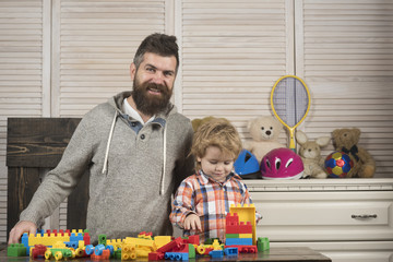 Fatherhood concept. Father and son play together in playroom