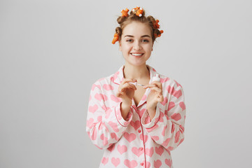 Girl is expert in beauty questions. Portrait of good-looking cozy woman in hair curlers and pyjamas with heart template painting nails while standing against gray background. Home concept