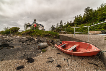 Stromeferry, Scotland - June 10, 2012: Red sloop rests on dry land at shore of Loch Carron among debris. White house and forested hill in back. Under cloudscape.