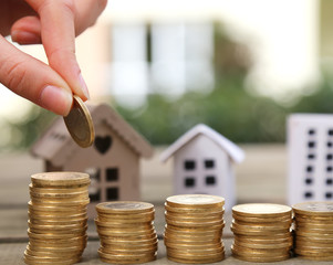 Women hand putting money coins stack growing with house and sunlight background. Business growth investment and financial concept ideas.