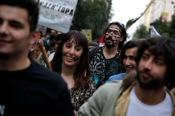 A protester with his face painted like razor wire takes part in a demonstration to mark United Nations day against racism in Athens
