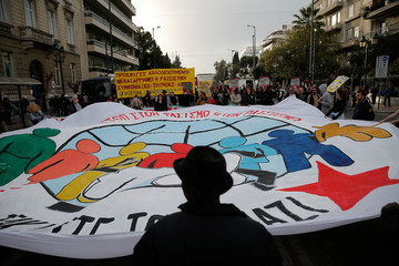 Protesters hold a banner during a demonstration to mark United Nations day against racism in Athens
