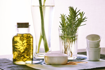 oil jar with herbs and rosemary green on the table in the daylight