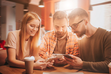 Nice picture of three friends sitting together and holding phones in their hands. They are playing games. This people are happy but concentrated.