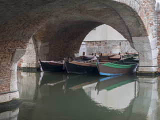 three fishing boats on the canal under an ancient brick arch in Comacchio in Italy