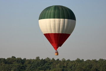 Obraz Balon na rozgrzane powietrze, w pasy zielony, biały i czerwony, w powietrzu, ponad drzewami - fototapety do salonu