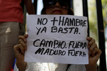 """A woman holds a placard that reads """"No more hunger. Stop. Change. Out Maduro Out"""" during a gathering of opposition supporters in Caracas"""
