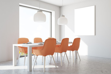 White dining room, orange chairs, poster
