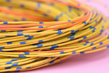 Colored electrical cable on pink background