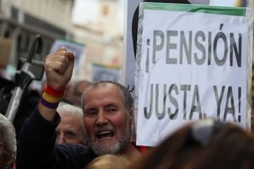 """A man shouts slogans beside a placard reading """"Fair Pension Now"""" during a demonstration demanding higher state pensions, in Madrid"""