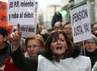 "A woman shouts slogans beside a placard reading ""Fair Pension Now"" during a demonstration demanding higher state pensions, in Madrid"
