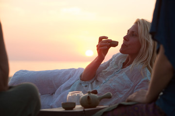young  woman drink tee on sunset background