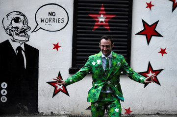Man dressed in a Shamrock suit walks past a mural on St. Patrick's Day in Dublin