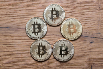 Physical bitcoin coins on wooden background