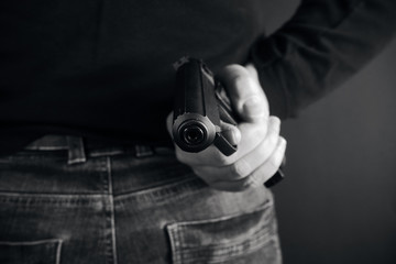 Man pointing a gun at the target on dark background, selective focus on front gun black and white photo