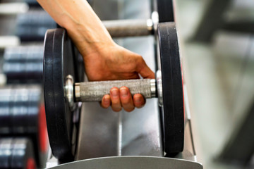 Hand grabs dumbbell in modern gym