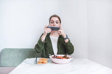 A cute girl sits at the restaurant at the table and takes a photo of her food on the camera of the smartphone. Woman photographs food on the phone.