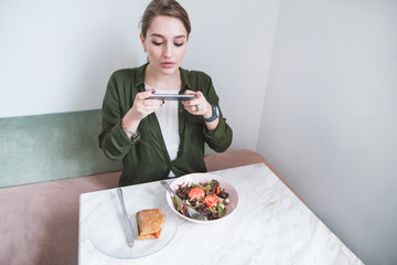 A blogger girl makes a photo of food on the phone. Woman sitting in a restaurant and photographing food at lunch time.
