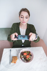A young, pretty woman makes a photo of her food at the restaurant. A blogger photographs a sandwich and a salad on a smartphone