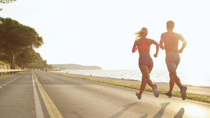 Keuken foto achterwand Jogging COPY SPACE: Athletic young couple jogging near the sea on perfect day in summer