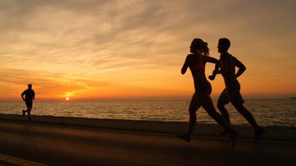 SILHOUETTE: Orange sun rays illuminate athletic man and woman on evening jog.