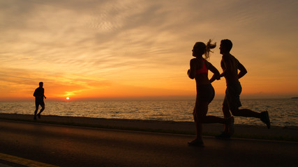 SILHOUETTE: Fit people run along silent ocean road in front of summer sunset.