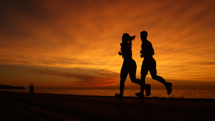 SILHOUETTE: Young man and woman doing their evening workout at gorgeous sunset.