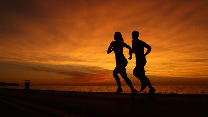 SILHOUETTE: Unknown athletic couple running along calm ocean at orange sunset.