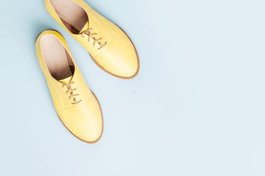 Stylish yellow shoes on pale blue background, flat lay