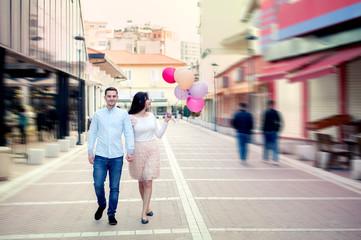 Happy couple walking with balloons in central street of Tirana, Albania, at the New Bazaar, or Pazari i ri