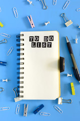 Open notebook on a blue background with an inscription. To do list. Stationery is in disarray. Beautiful background with place for text. Mock up.