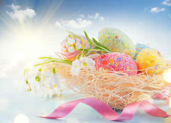 Fotoväggar - Easter holiday scene background. Traditional colorful eggs and spring flowers in the nest over blue sky, border design