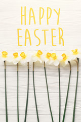 happy Easter  text. beautiful fresh daffodils on white wooden background top view. bright yellow flowers on rustic wood flat lay. floral greeting card. easter greetings concept