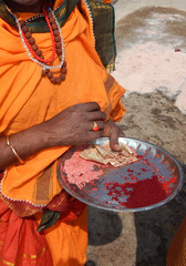 Indian Hindu sadhu standing in a temple to apply kumkum or red powder on forehead of devotees and receives donations